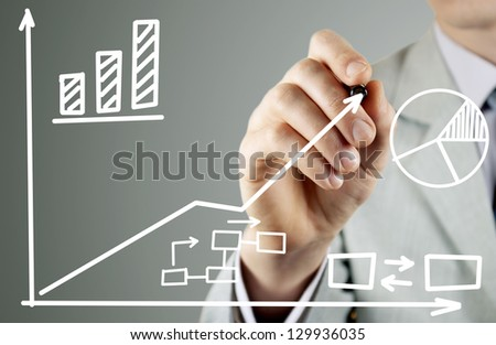 man in a business suit writing on a transparent screen during a presentation - stock photo