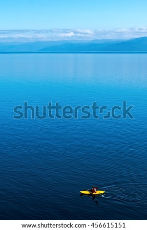 man in a canoe floating on Lake Baikal, summer day