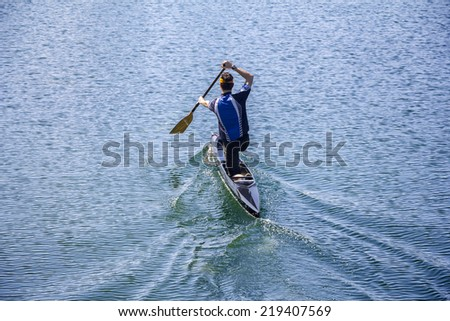 Man in a canoe, rowing on the tranquil lake - stock photo