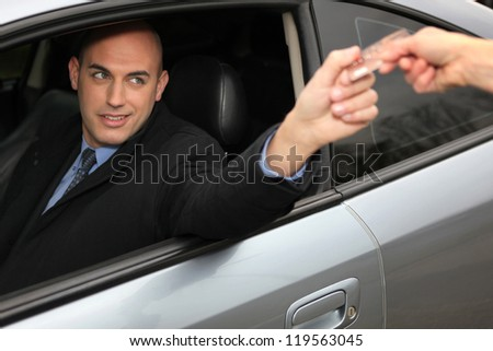 Man in a car using a credit card - stock photo