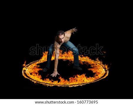 Man in a circle of fire Blazing flames over black background - stock photo