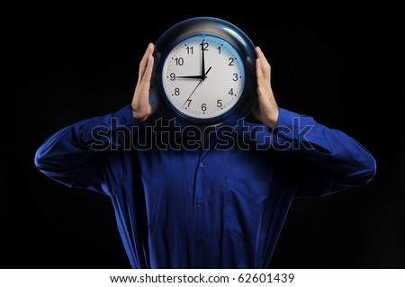 man in a dark blue shirt holds hours in the face of - stock photo