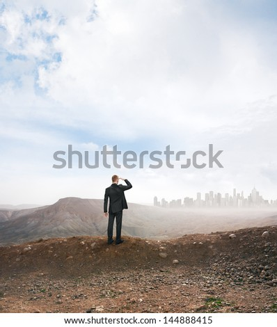 man in a desert looking at the city - stock photo
