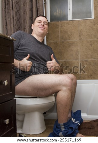 Man in a dirty bathroom giving the thumbs up - stock photo