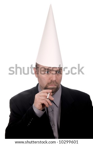 Man in a dunce cap smoking a cigarette over a white background - stock photo