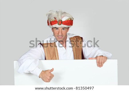 Man in a fancy dress turban giving the thumbs up to a board left blank for your image