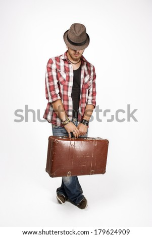 Man in a full-length with a hat on face and a suitcase in hands. Isolated on white background. - stock photo
