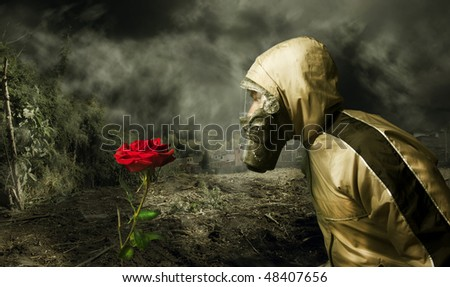 Man in a gas mask looking at a rose - stock photo