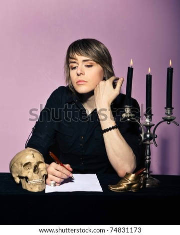 man in a gothic setting writes a letter - stock photo
