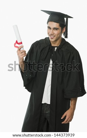 Man in a graduation gown holding a diploma