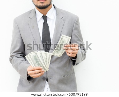 Man in a gray suit holds out hand with US dollars,businessman giving cash dollars to the client. Concept of finance success, Money and business topic: hand in a suit holding a banknote of 100 dollars