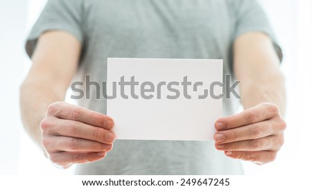 Man in a grey t-shirt holding a blank white card in his extended hands with copyspace for your text or advertisement. - stock photo