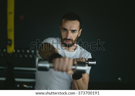 man in a gym exercising with weights. Dark background