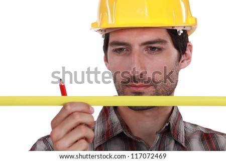 Man in a hardhat with a pencil and measure - stock photo