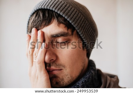 Man in a hat with a headache - stock photo