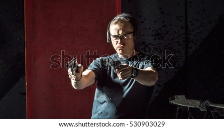 Man in a headphones with a gun in his hand on the dark background