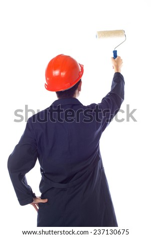 man in a helmet and  blue robe paint roller wall, turning his back - stock photo