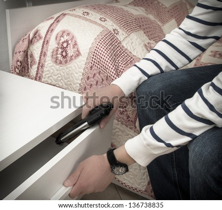 Man in a high crime area placing a handgun into the drawer of a bedside table in readiness to defend himself during a home invasion or attack and to ensure a good nights sleep - stock photo