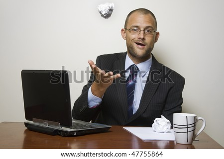 Man in a home office throwing a ball of paper in the air. - stock photo