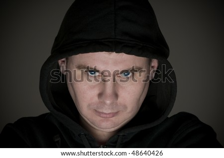 Man in a hood on dark background - stock photo