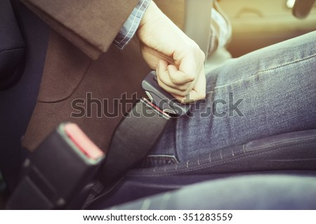 Man in a jacket and jeans buttons in the car seat belt, ready for the trip by car. Safety on the road, the driver's life. - stock photo