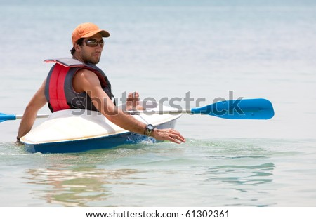Man in a kayak on the ocean enjoying his holidays - stock photo