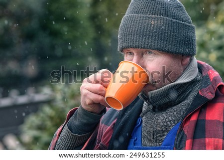 Man in a knitted wool beanie, jersey and jacket standing outdoors in the snowy winter weather drinking hot coffee from a bright orange mug - stock photo