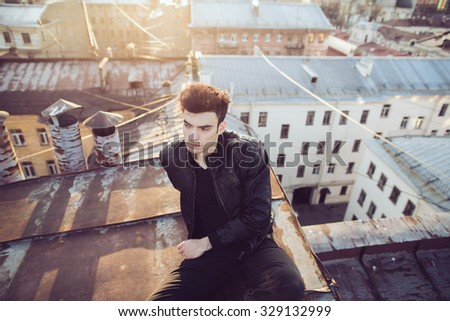 Man in a leather jacket on a rooftop in the center of the city - stock photo