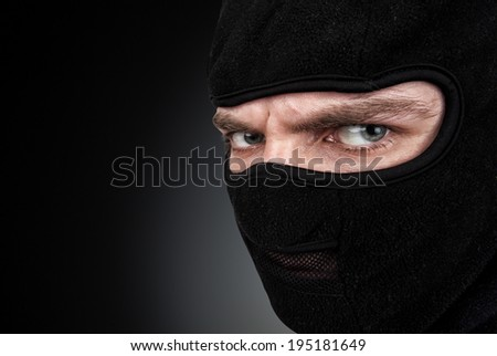 Man in a mask on black background - stock photo