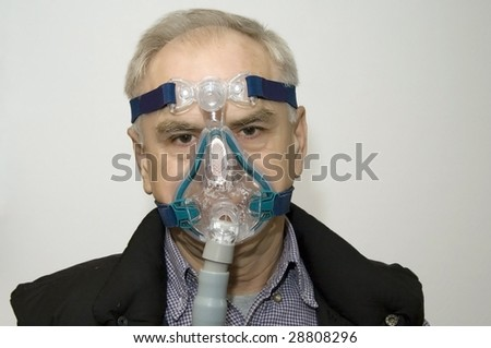 Man in a mask (sleep apnea disorder) - stock photo