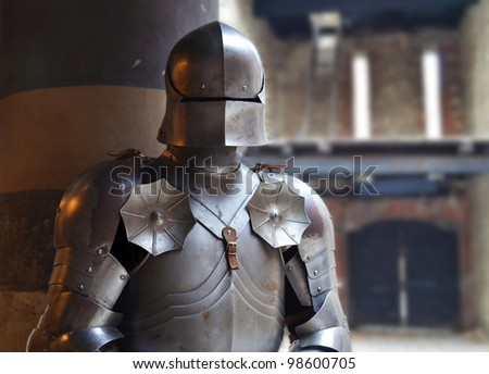 Man in a medieval armor with castle walls in background - stock photo