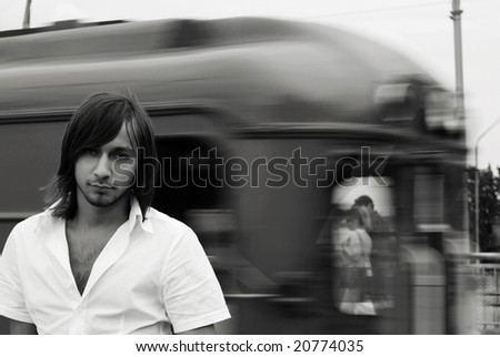Man in a metro station with blurred by motion train on the background - black and white