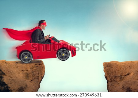 man in a red car jumping a ravine - stock photo