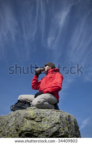 Man in a red jacket at the summit - stock photo