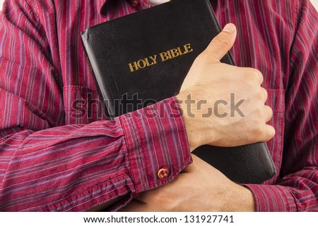 Man in a red shirt hugging the Holy Bible - stock photo
