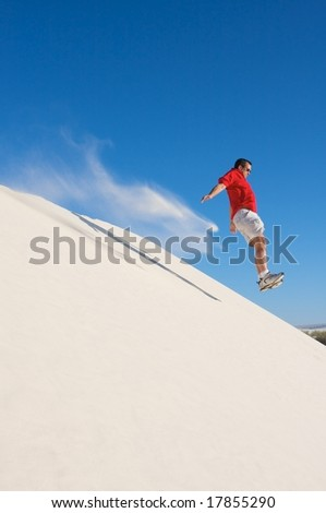 Man in a red shirt taking a leap off the top of a white sand dune with a blue sky - stock photo