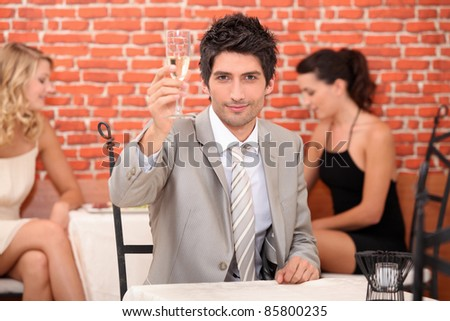 Man in a restaurant with a glass of champagne - stock photo