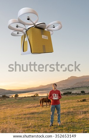 Man in a rural environment guiding a drone carrying a package - stock photo