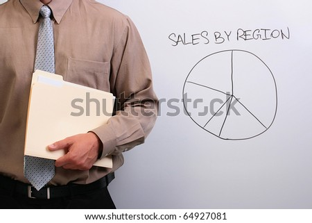 Man in a shirt and a tie holding a manila folder next to a drawing of a pie chart. - stock photo