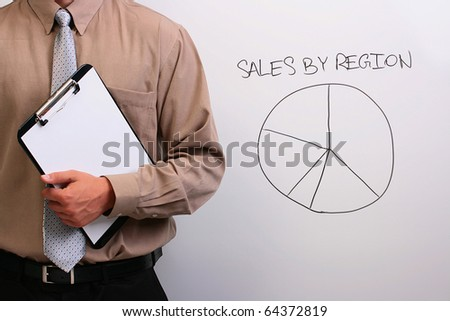 Man in a shirt and a tie standing next to a drawing of a pie chart. - stock photo