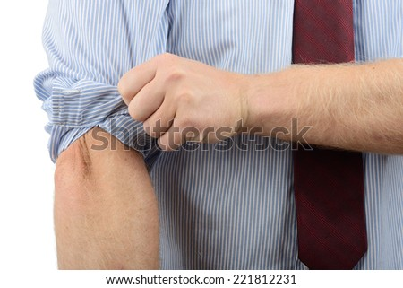 Man in a shirt getting ready to do some work by rolling up his sleeves - stock photo