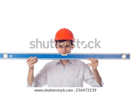 man in a shirt in orange construction helmet look at builder level; isolate background - stock photo