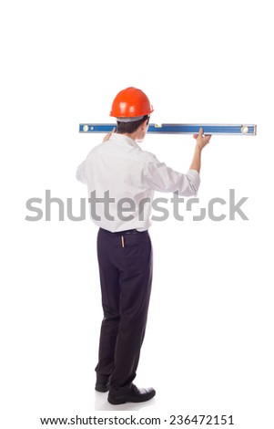 man in a shirt in orange construction helmet look at builder level; isolate background; isolate background; turn your back - stock photo