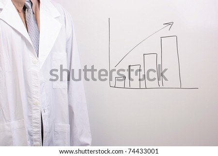 Man in a shirt, tie, and a white lab coat standing next to a drawing of a bar graph. - stock photo