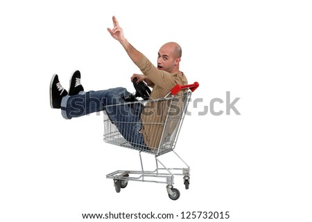 Man in a shopping trolley - stock photo