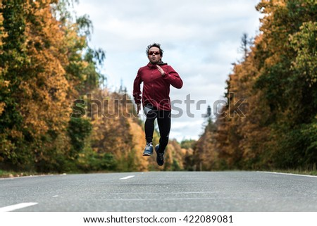 Man in a sports uniform and glasses running down the road in the autumn forest - stock photo