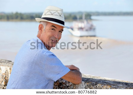 Man in a straw hat watching a ferry cross the Gironde estuary - stock photo