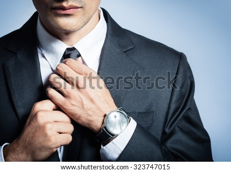 Man in a suit fixing his tie. - stock photo