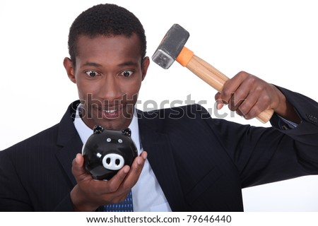 Man in a suit hammering open a child's piggy bank - stock photo