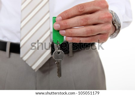 man in a suit holding a key - stock photo